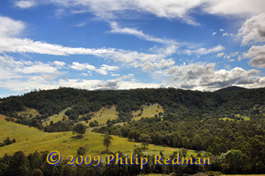 Single house set amongst a tree covered hilside near Dungog, New South Wales with a backdrop or cloud formations.