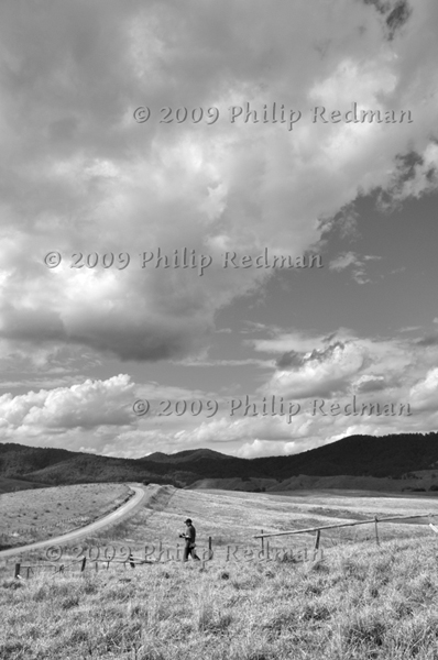 Black and white image of lone Photographer in open countryside walking through a paddock of almost white grass with masses of beautiful clouds gathering.